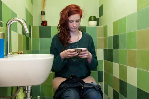 gallery-1441378605-reading-phone-on-toilet